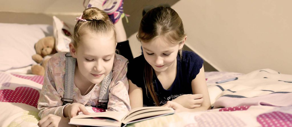 girls reading in bed