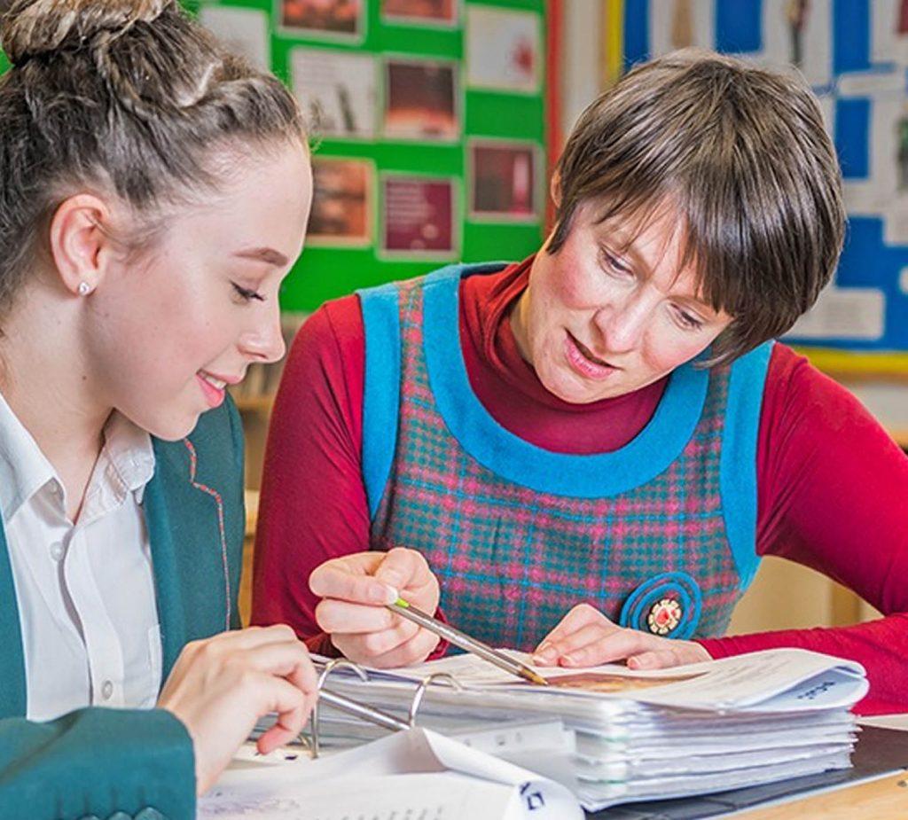 teacher helping girl with work