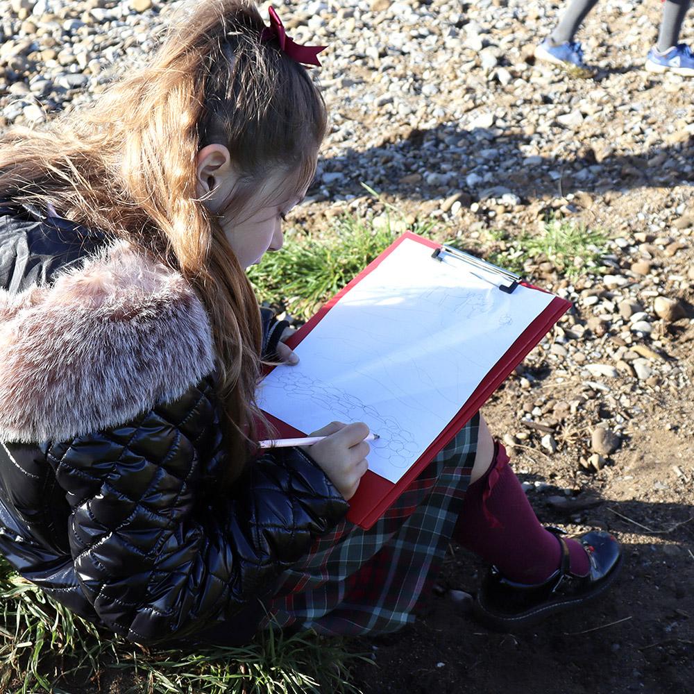 girl drawing on clipboard