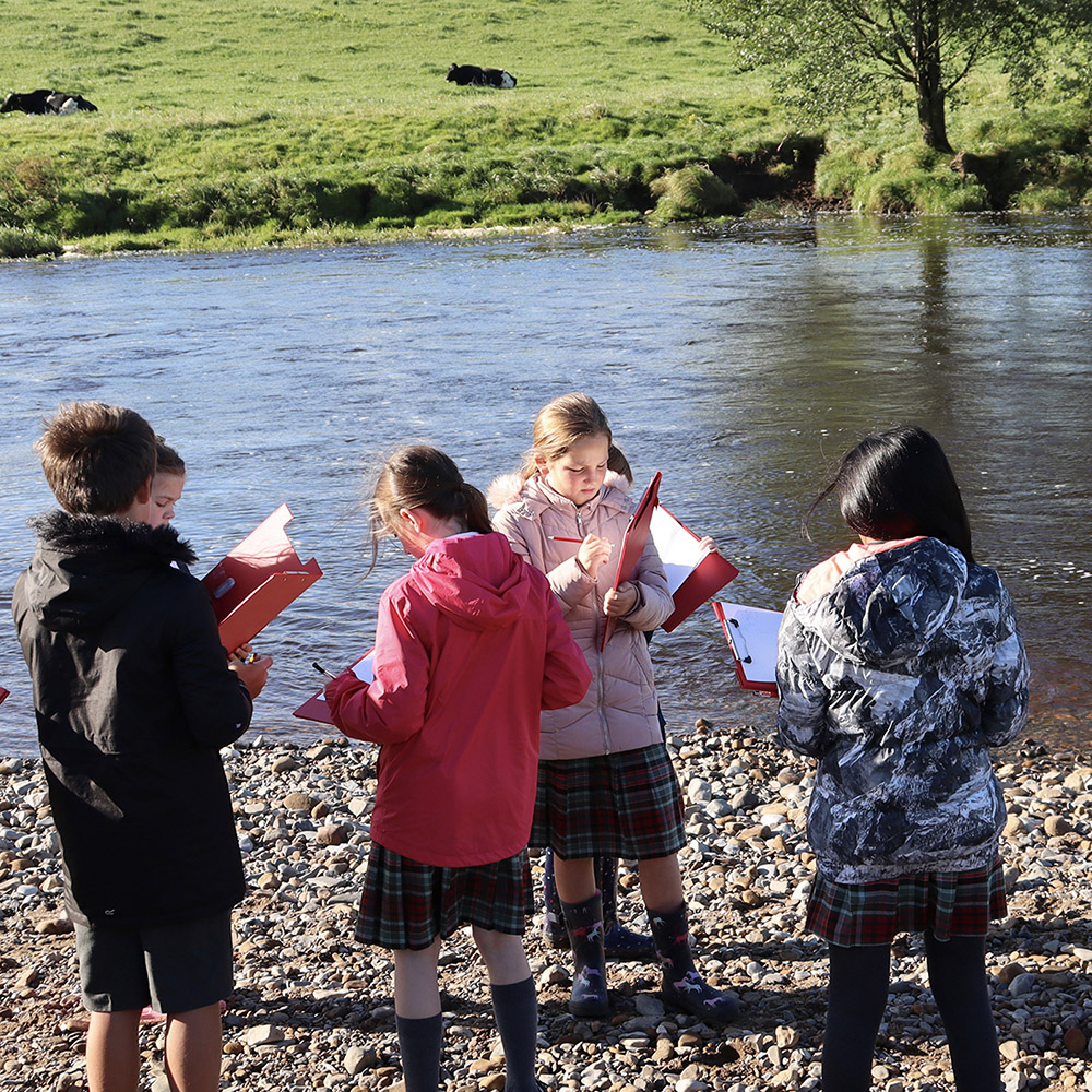 class next to river with clipboards