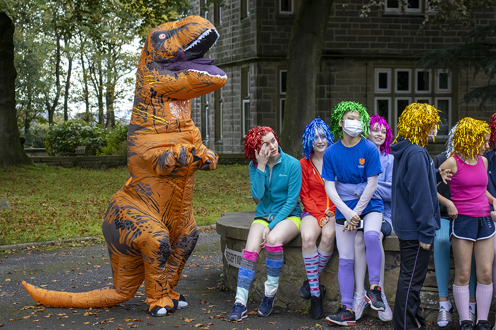 students in costumes with dinosaur