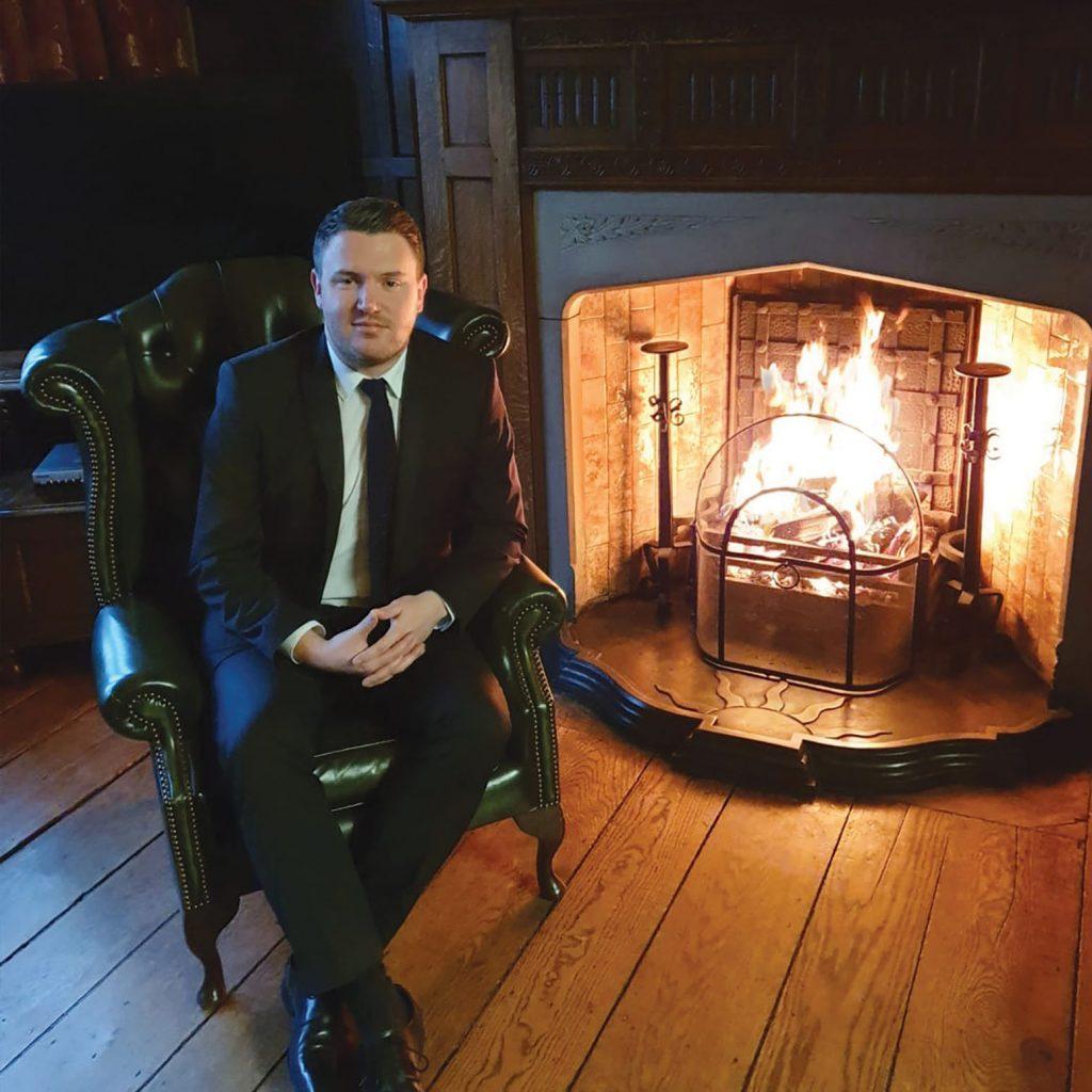 man sitting next to fire