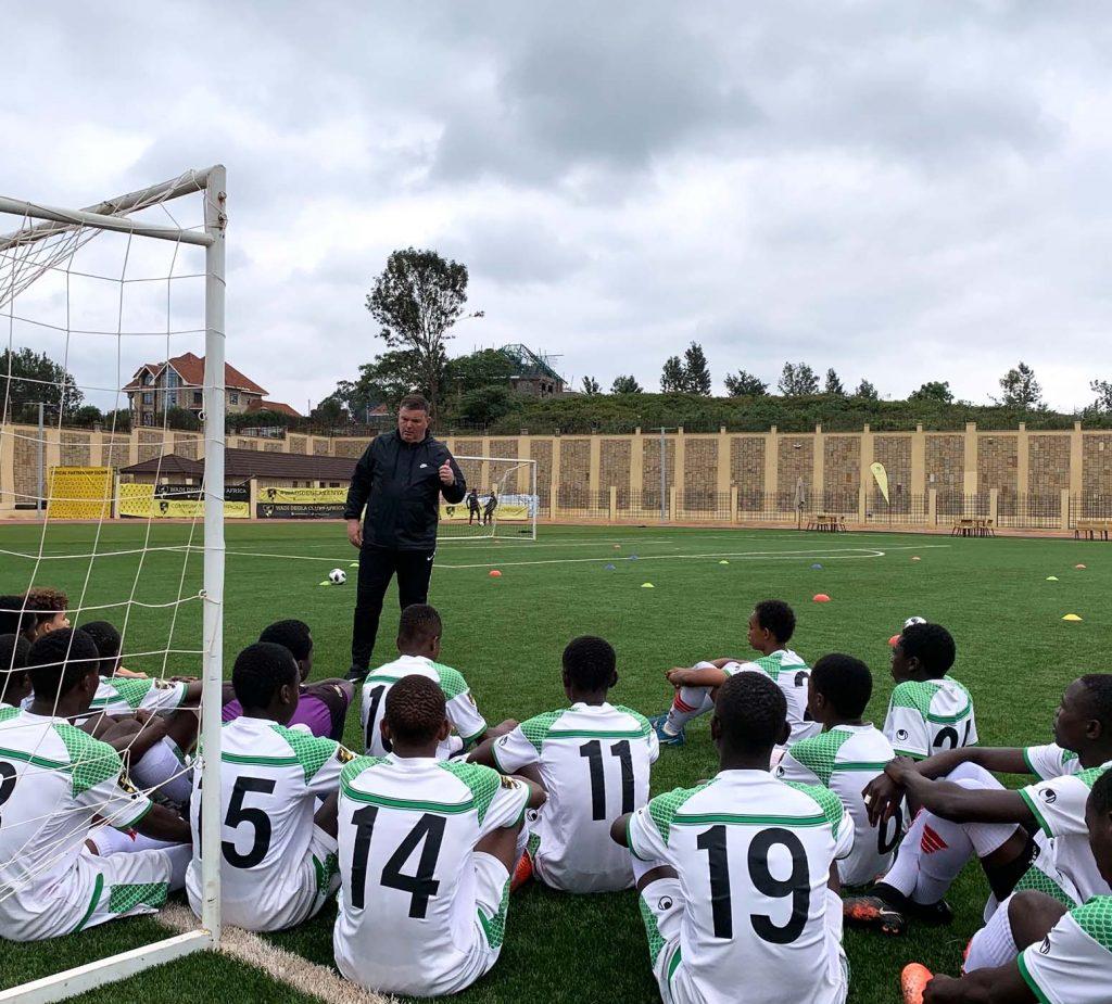 coach instructing football team