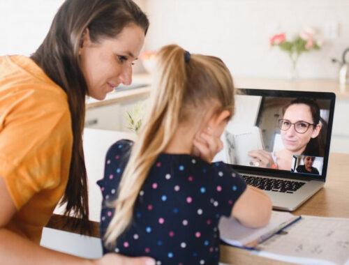 Teacher assisting girl on laptop